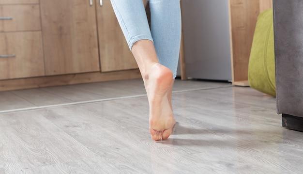 Vrouwelijke voeten lopen op de vloer thuis.