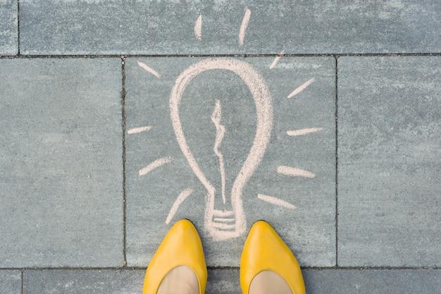 Vrouwelijke voeten met abstracte afbeeldingstekening van gloeilamp