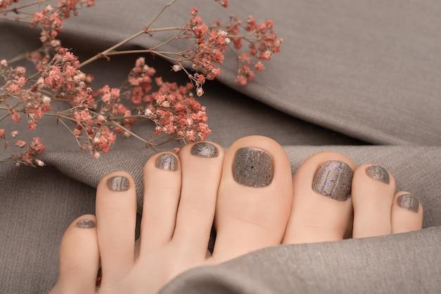 Vrouwelijke voeten met beige nageldesign op grijze stoffen oppervlak.