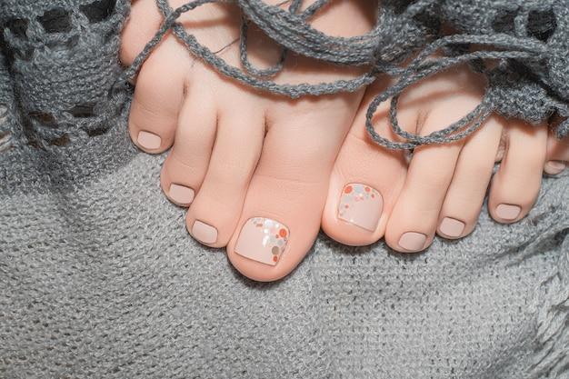 Vrouwelijke voeten met beige nagellak op grijze stof.