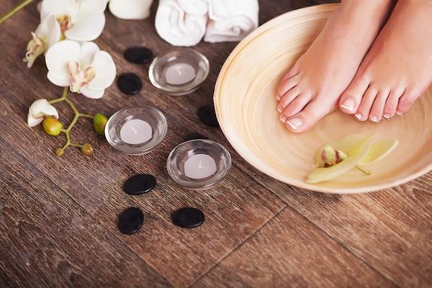 Vrouwelijke voeten met druppels water, spa kommen, handdoeken, bloemen en kaarsen.