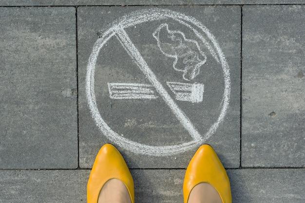 Vrouwelijke voeten met foto niet roken geschilderd op de grijze stoep