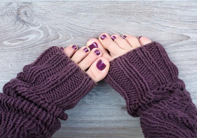 Vrouwelijke voeten met pedicure in bruine sokken