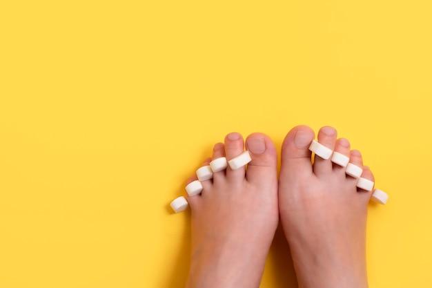 Vrouwelijke voeten met spons voor pedicure op vingers op heldere gele achtergrond met kopie ruimte.