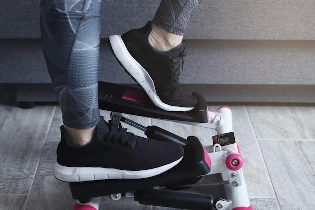 Vrouwelijke voeten op fitness machine