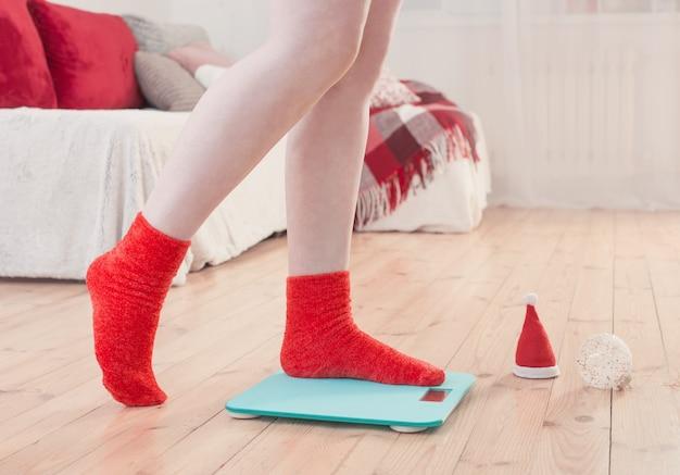 Vrouwelijke voeten staan op blauwe elektronische weegschaal voor gewichtscontrole in rode sokken met kerstversiering