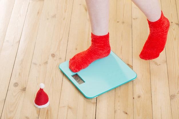 Vrouwelijke voeten staan op elektronische weegschaal voor gewichtsbeheersing in rode sokken met kerstmuts op houten vloer