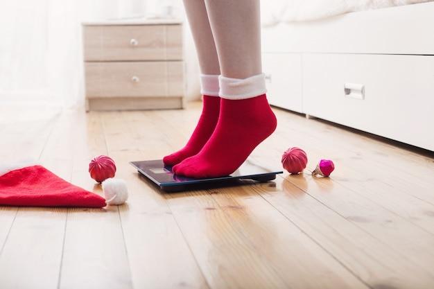 Vrouwelijke voeten staan op elektronische weegschalen voor gewichtsbeheersing in rode sokken met kerstversiering