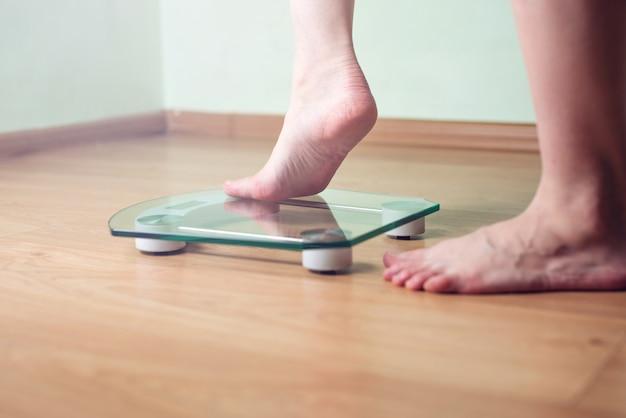 Vrouwelijke voeten staan op elektronische weegschalen voor gewichtsbeheersing