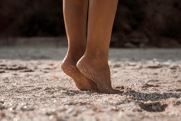Vrouwelijke voeten staan op hun tenen op een zandstrand op een zomerdag.