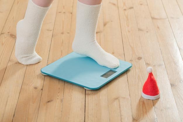 Vrouwelijke voeten staande op blauwe elektronische weegschaal voor gewichtsbeheersing met kerst kerstmuts op houten vloer