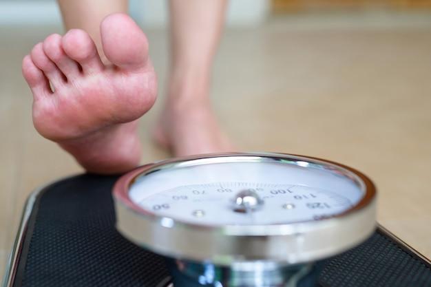 Vrouwelijke voeten staande op elektronische weegschaal voor gewichtscontrole op houten achtergrond. het concept van afvallen en afvallen