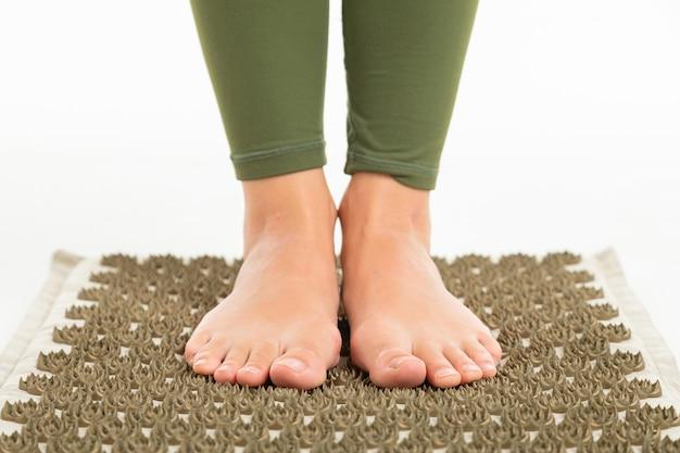 Vrouwelijke voeten zonder schoenen staat op een sportmat