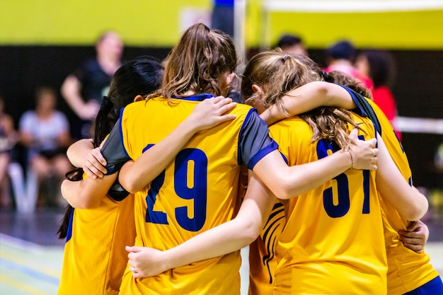 Vrouwelijke volleyballers die bij elkaar komen voordat ze het spel beginnen