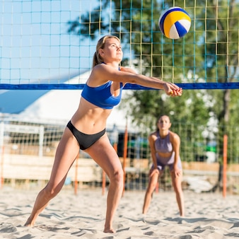 Vrouwelijke volleyballers spelen op het strand