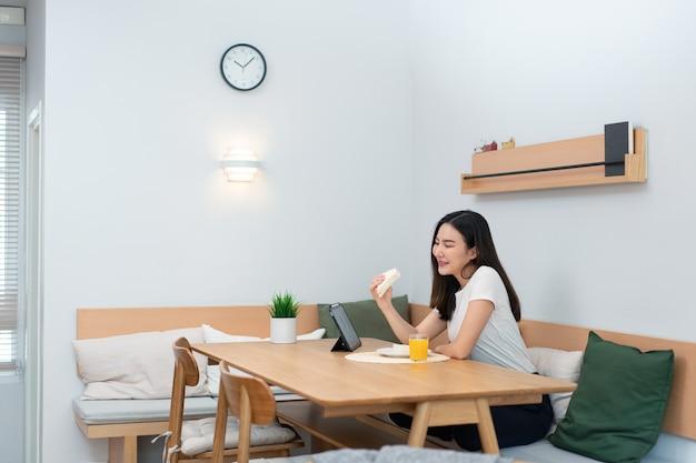 Vrouwelijke volwassene geniet van het eten van sandwiches en sinaasappelsap en kijkt naar online media