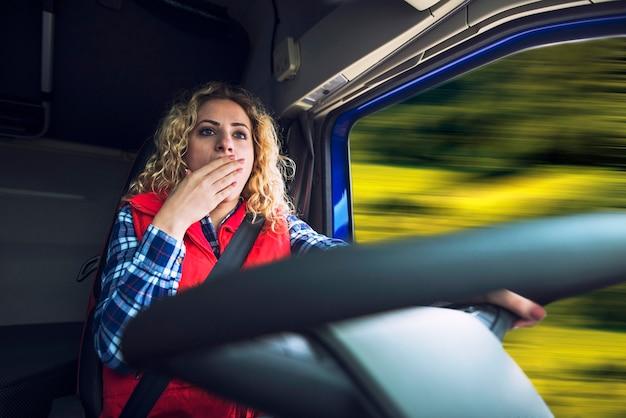 Vrouwelijke vrachtwagenchauffeur geeuwen vanwege vermoeidheid en verveling tijdens het besturen van een vrachtwagen