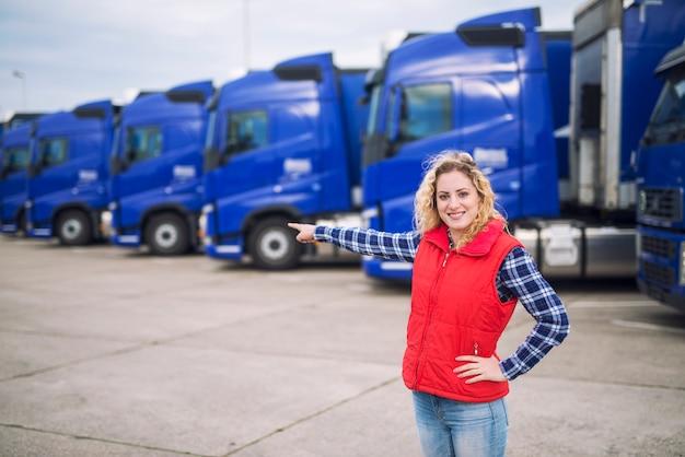 Vrouwelijke vrachtwagenchauffeur staande voor geparkeerde vrachtwagens en haar vinger naar de transportvoertuigen