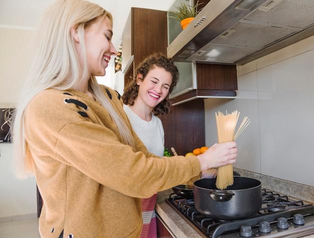 Vrouwelijke vriend die haar glimlachende blonde jonge vrouw bekijkt die spaghetti voorbereidt