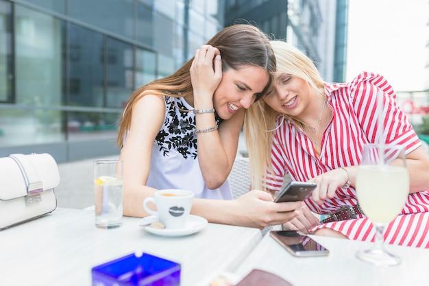 Vrouwelijke vrienden die bij koffie met koffie zitten die mobiele telefoon met behulp van