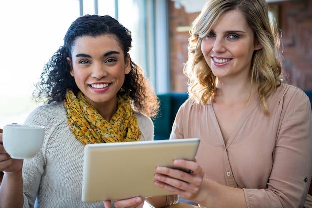 Vrouwelijke vrienden die digitale tablet gebruiken terwijl het hebben van koffie