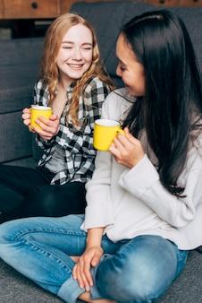 Vrouwelijke vrienden die en thee spreken drinken