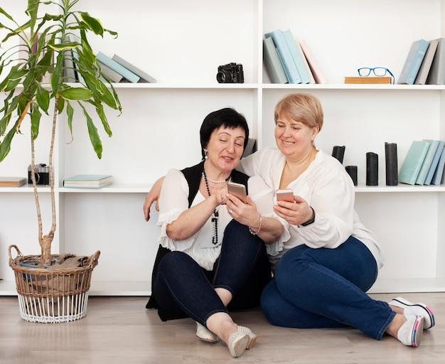 Vrouwelijke vrienden die hun telefoons bekijken
