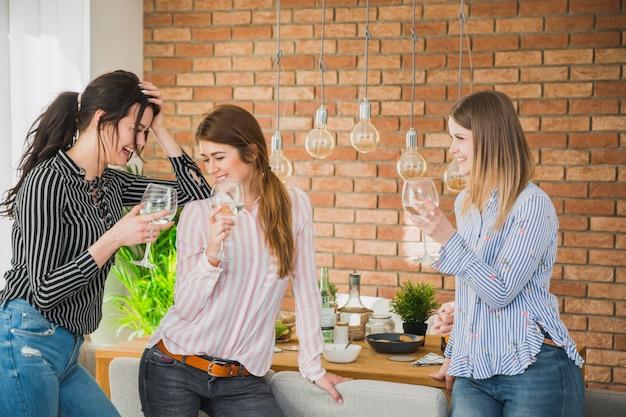 Vrouwelijke vrienden die in baksteenruimte lachen