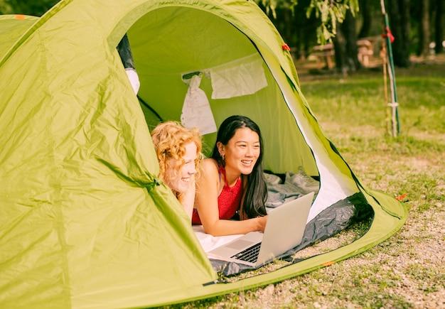 Vrouwelijke vrienden die in tent met laptop liggen