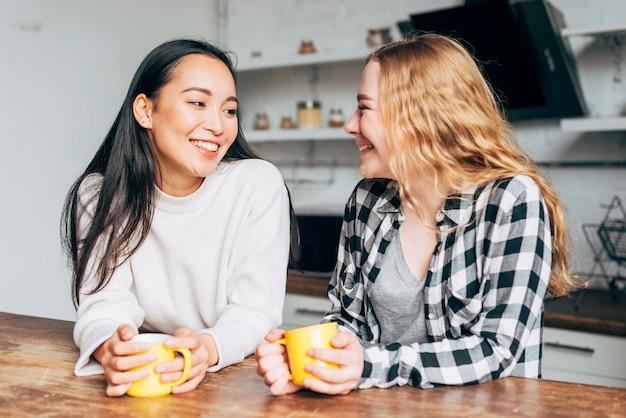 Vrouwelijke vrienden die met kop theeën spreken