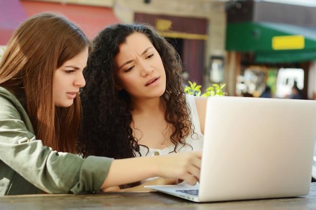 Vrouwelijke vrienden die met laptop in een koffiewinkel bestuderen.