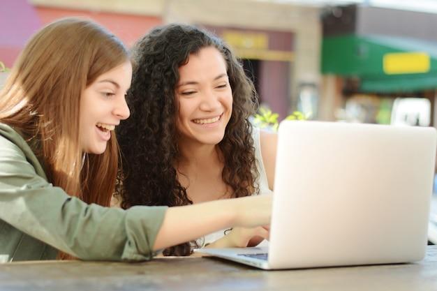 Vrouwelijke vrienden die met laptop in een koffiewinkel bestuderen