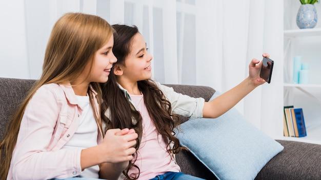 Vrouwelijke vrienden die op bank zitten die selfie op slimme telefoon nemen