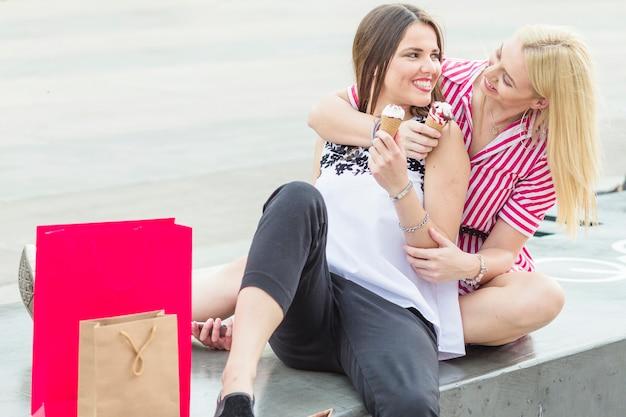 Vrouwelijke vrienden die op bank zitten die van de roomijskegel genieten