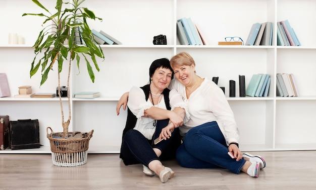 Vrouwelijke vrienden die op de vloer en de installatie zitten