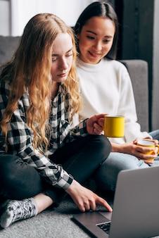Vrouwelijke vrienden die op film op laptop letten
