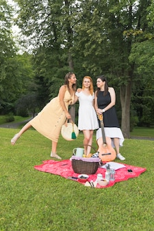 Vrouwelijke vrienden die op picknick in de tuin genieten van