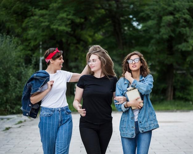 Vrouwelijke vrienden die samen op parkbestrating lopen