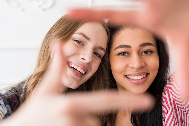 Vrouwelijke vrienden die selfie bij camera gesturing