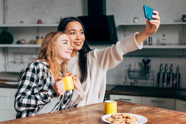 Vrouwelijke vrienden die selfies thuis maken