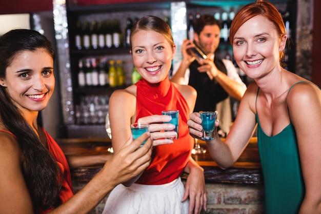 Vrouwelijke vrienden die van tequila in nachtclub genieten