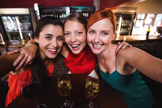 Vrouwelijke vrienden die van wijn in nachtclub genieten