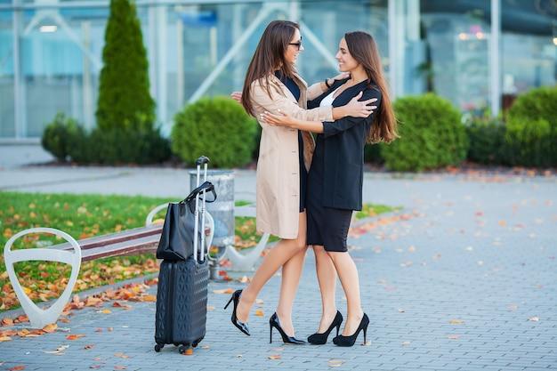 Vrouwelijke vrienden gaan samen op reis. vooraanzicht van schattige brunettes met bagage op de luchthaven