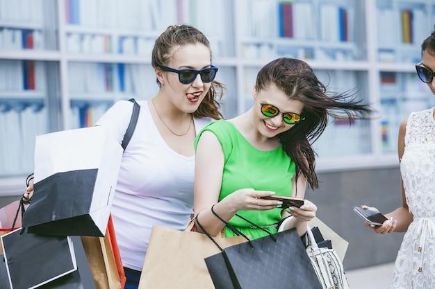 Vrouwelijke vrienden op straat tijdens het winkelen met pakketten en mobiele telefoons