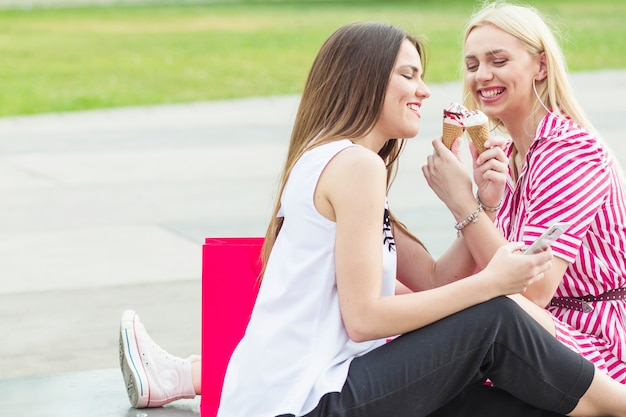 Vrouwelijke vrienden zitten in de tuin genieten van ijs kegel