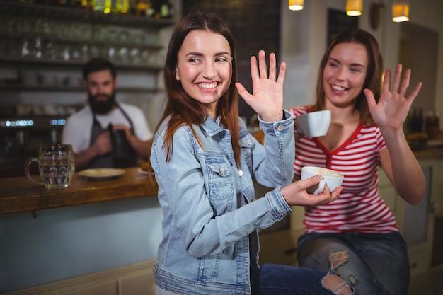 Vrouwelijke vrienden zwaaiende handen onder het genot van een kopje koffie