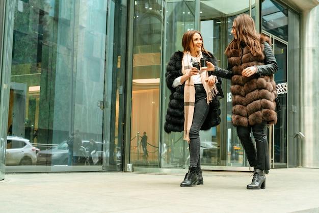 Vrouwelijke vriendschap, relaties. twee meisjes drinken koffie op straat in de buurt van glazen kantoorgebouwen, een bedrijf, een bank. het einde van de werkdag van de manager. koffie op de vlucht.