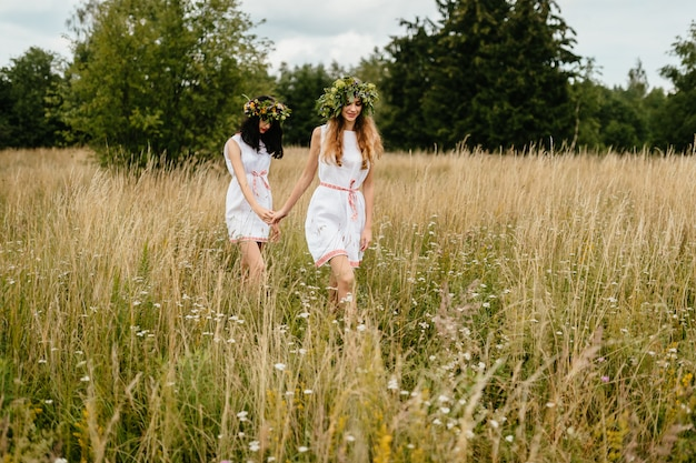 Vrouwelijke vriendschap. stemmingsportret van twee mooie slavische verschijning jonge meisjes in etnische jurken en bloemenkrans wandelen in de natuur. vrienden vrije tijd. hand die hand houdt