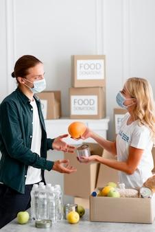 Vrouwelijke vrijwilliger die donaties uitdeelt voor voedseldag