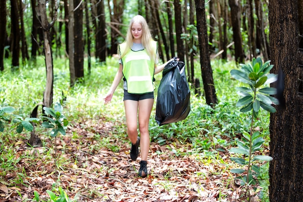 Vrouwelijke vrijwilliger die een plastic afvalzak houdt, het vuilnis oppakt en het in een zwarte vuilniszak stopt.